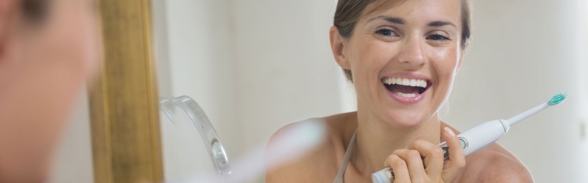 A woman is smiling while holding a toothbrush
